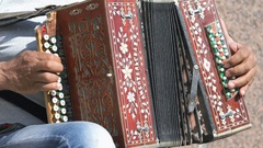 Adult man sitting on a chair plays the accordion Arkistovideo
