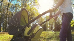 The father cradles a child in stroller Stock Footage