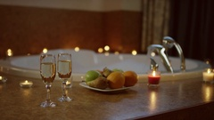View of glasses of champagne and plate with fruits standing near jacuzzi Stock Footage