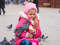 The girl was frightened brazen pigeon who jumped into his arms for a crust .. Stock Photos