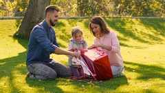 Sunny family opening their daughter is present together Stock Footage
