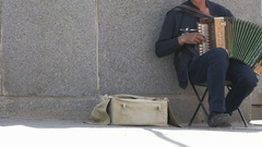 Tanned man aged 60s plays the accordion outdoors Arkistovideo