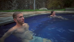 A young handsome man relaxing in the hot sulfur spring slow motion Stock Footage