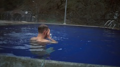 A young handsome man diving and coming out of the hot sulfur spring slow motion Stock Footage