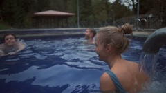 Cheerful young friends swimming in the hot sulfur spring motion Stock Footage