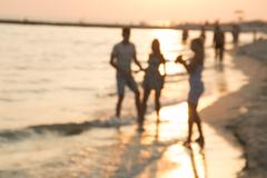 Summer Holiday or Vacation idea. Silhouettes of young people in sea at sunset Stock Photos
