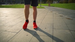 Young man warming up ankles, doing leg turning in the beautiful park slow motion Stock Footage