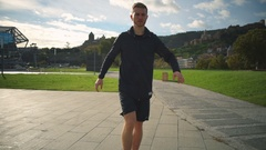 Young man warming up, doing leg, hip turning in the beautiful park slow motion Stock Footage