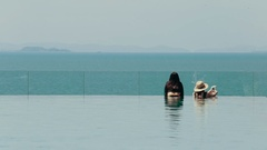 Girls in luxury hotel looking at the ocean. The blue tones Stock Footage