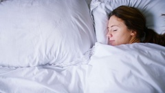 4K Young woman wakes up in bed and reaches across to find herself alone Stock Footage