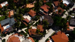Flying over the houses, palm brown roof Stock Footage