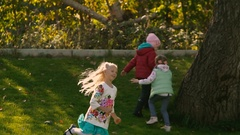 Little blond girl playing with other children on field Stock Footage
