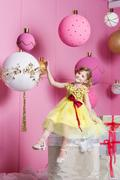 Pretty girl child 6 years old in a yellow dress. Baby in Rose quartz room Stock Photos
