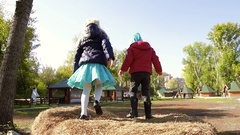 Two charming girls play in the fall in the street on a haystack Stock Footage
