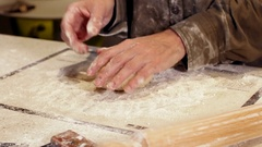 Woman baker presses dough ball onto counter - close up Stock Footage
