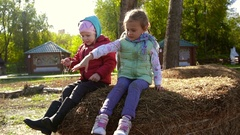 Two little girls sitting on a haystack and throwing hay down Stock Footage