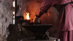 Blacksmith forging the molten metal on the anvil in smithy Stock Footage