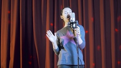 Pretty girl singing on a stage at a party with lights on background Stock Footage