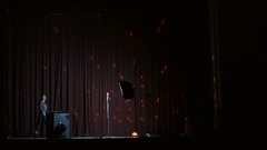 Pretty girl singing on a stage with lights on background Stock Footage