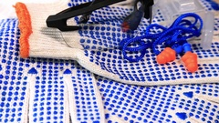 Thin work gloves with  blue pimples, protective glasses and ear plugs Stock Footage
