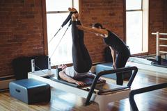 Trainer helping a woman while practicing pilates Stock Photos