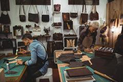 Attentive craftswoman hammering leather Stock Photos
