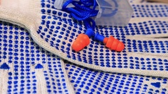 Thin work gloves with  blue pimples, and ear plugs on a rotating surface, Stock Footage