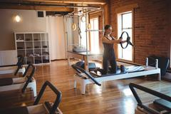 Woman practicing pilates on reformer using exercise ring Stock Photos