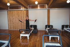 Woman practicing pilates on reformer Stock Photos