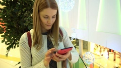Beautiful young woman with smartphone in mall. Browsing internet, communicating Stock Footage