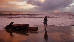 Silhouette of a girl. she looks at storm sea in sunset time. waves reach up to Stock Footage