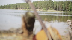 Acoustic Guitar forgotten on the shore of the lake near the old stump with roots Stock Footage