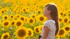 Happy teenager girl with hair flying in the wind walks in a field of yellow Stock Footage