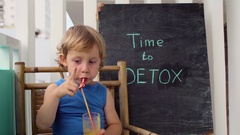 TIME TO DETOX chalk inscription. The boy is drinking fresh, healthy, detox drink Stock Footage