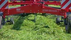 Red machinery is turning freshly cut grass around Stock Footage