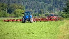 Blue and red tractor are cutting grass on the field Stock Footage