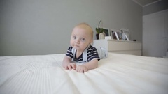 Cute baby lying on his stomach on the big bed. Stock Footage