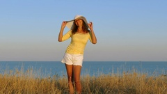 4K.Adult Woman in yellow blouse and hat dance and smile on  sea coast Stock Footage