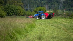 Big blue tractor with a huge grass cutting machine connected to it Stock Footage