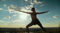 Woman practicing yoga in the park at sunset - hero pose Virabhadrasana Stock Footage