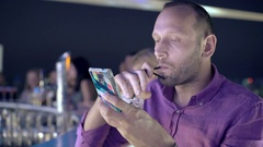 Young man using smartphone and drinking beverage in bar at night Stock Footage
