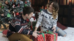 Happy couple, sitting near the new year tree and opening gifts. Stock Footage