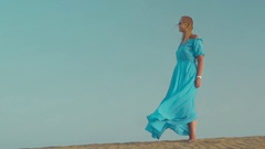 Woman in blue dress on the beach Stock Footage