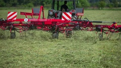 Tractor is pulling big rotary hay rakes behind it Stock Footage