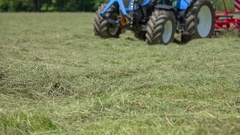 Blue tractor is making a turn on a big lawn Stock Footage