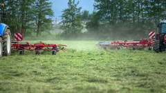 Three tractors are working outside on the grass fields Stock Footage