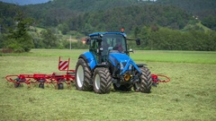 Turning hay around with rotary hay rakes Stock Footage