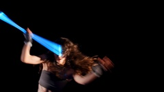 Beautiful woman dance with neon staffs in ultraviolet light, gipsy show Stock Footage