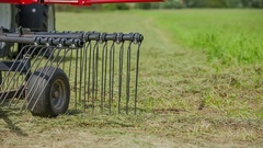 Tractor and rotary hay rakes start working on the mown grass Stock Footage