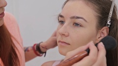Close up shot. Professional make-up artist applying powder to woman face Stock Footage
